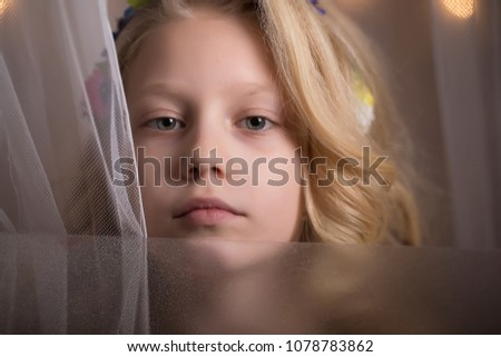 Close-up portrait of small girl. Face. Child. She looking at camera with blonde hair. White curtain. Blur background. Professional photo session. Professional photo studio. #1078783862