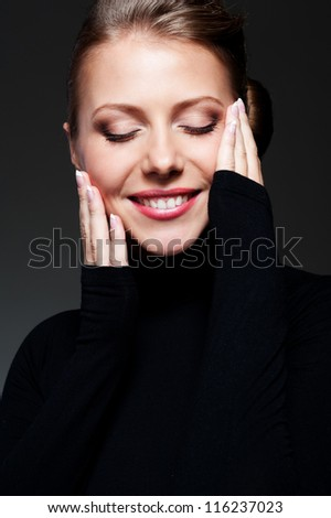 close up portrait of smiley and alluring female against dark background