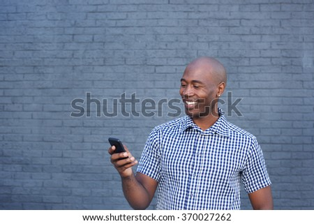 Close up portrait of smiling african man looking at mobile phone