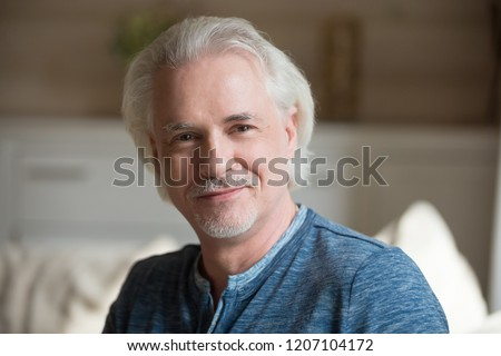 Close up portrait of smiling aged man with moustache looking at camera relaxing at home, happy senior male posing shooting indoors, elderly husband making professional photo or picture for album