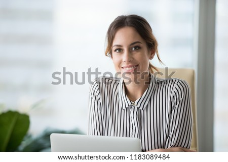 Close up portrait of smiling beautiful millennial businesswoman or CEO looking at camera, happy female boss posing making headshot picture for company photoshoot, confident successful woman at work Stock photo ©
