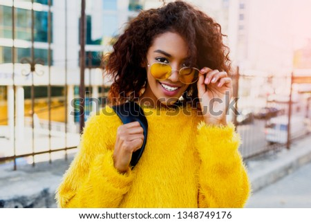 Close  up portrait  of  smiling black woman in the stylist yellow sweater and sunglasses enjoying sunny day. College girl walking over the city.