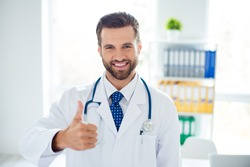 Close up portrait of smiling doctor recommending the new way of treatment by showing thumb up