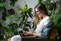 Close up portrait of smiling female gardener in glasses wear linen dress, sitting on chair in greenhouse, using laptop and speaking on web call surrounded by exotic plants. Home gardening, freelance