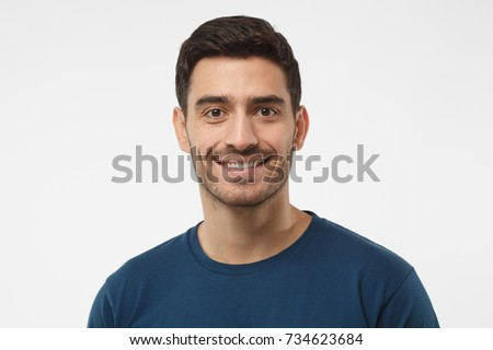 Close up portrait of smiling handsome guy in blue t-shirt isolated on gray background #734623684