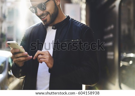 Close up portrait of smiling handsome trendy dressed hipster guy booking tickets on website of airplane company planning to visit foreign countries using smartphone and fast 4G internet connection
