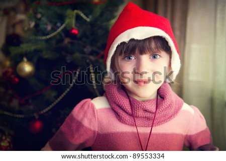 Close-up portrait of smiling Little Red Riding Hood in front of Christmas tree