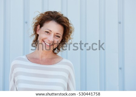 Close up portrait of smiling older woman standing outside