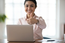 Close up portrait of smiling satisfied indian businesswoman show thumb up recommend online computer program. Happy ethnic female employee use laptop give recommendation to distant work or training.