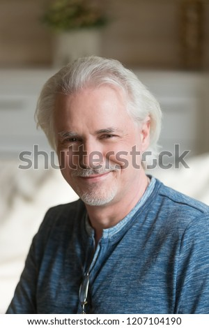Close up portrait of smiling senior man with moustache posing for album picture, happy aged male looking at camera relaxing at home, elderly husband feel positive shooting indoors, making photo