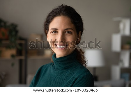 Close up portrait of smiling young Caucasian woman look at camera feel excited optimistic. Happy millennial 20s female renter or tenant overjoyed moving relocating to new home or apartment.