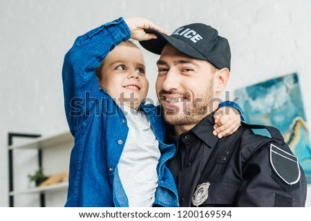 close-up portrait of smiling young father in police uniform carrying his little son and looking at camera Stock fotó ©