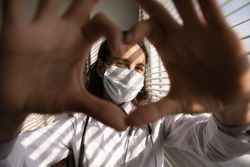 Close up portrait of smiling young female doctor in white medical uniform and facemask show heart love hand gesture. Happy woman GP in facemask show support, empathy and care. Corona concept.