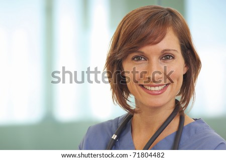 Close up portrait of smiling young woman doctor in scrubs - stock photo