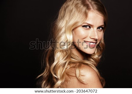 close-up portrait of smiling young woman with curly blond hair