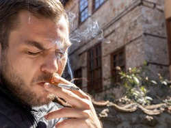 Close up Portrait of smoking young  adult man. He holding cigarette between fingers. Man inhale cigarette smoke.