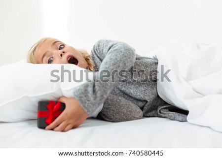 Close-up portrait of surprised female kid found a gift under the pillow