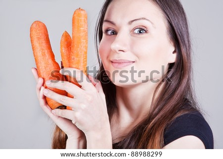 Close-up portrait of surprised young woman with three carrots in hands