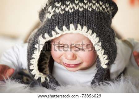 Close up portrait of sweet crying caucasian baby boy with grey cap lying on floor and looking down.