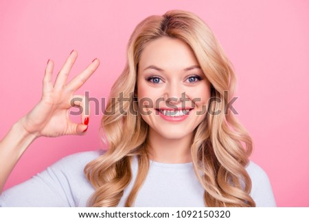 Close up portrait of sweet cute girl with modern hairstyle gesturing ok sign with fingers looking at camera isolated on pink background. Advertisement concept