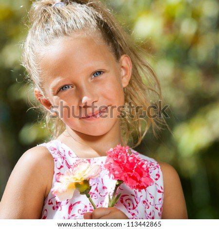 Close up portrait of sweet girl holding flowers in garden.