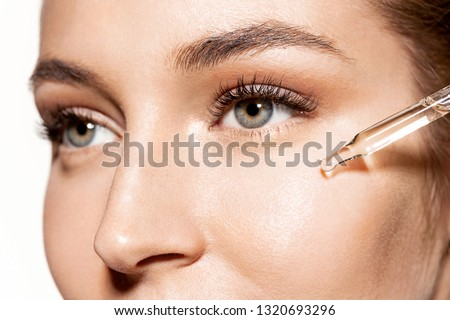 Close-up portrait of sweet girl with shiny skin applying drop of face oil. Beauty treatment and wellness concept. Cute model using modern cosmetology on white background #1320693296