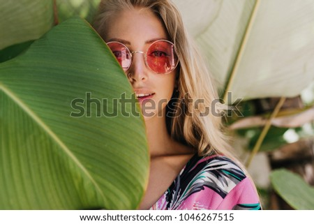 Close-up portrait of tanned european woman with interested face expression. Outdoor shot of refined fair-haired girl hiding beside green leaf with playful smile.