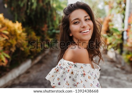 Close-up portrait of tanned woman on rest in light blouse. Curly dark-haired girl with snow-white smile looks into camera on background of tropical plants