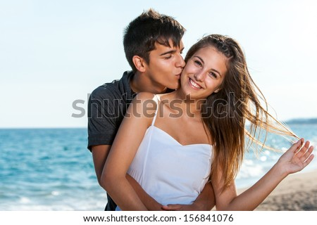 Close up portrait of teen couple embracing on beach.