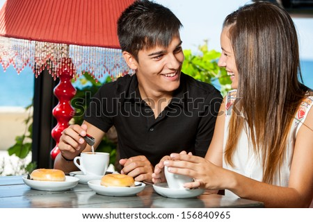 Close up portrait of teen couple enjoying breakfast in restaurant.
