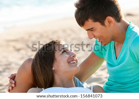 Close up portrait of teen couple sharing romantic moment on beach.