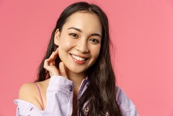 Close-up portrait of tender, beautiful young asian woman with clean skin, no pimples or blemishes, smiling lovely camera, touching neck and look camera romantic, stand pink background