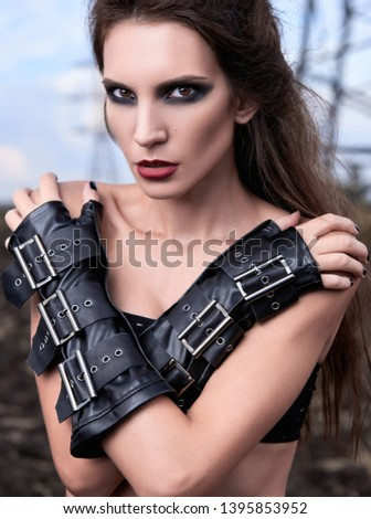 Close-up portrait of the lovely young gothic girl wearing black leather gloves
