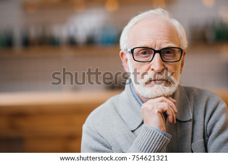 close-up portrait of thoughtful senior man looking at camera #754621321