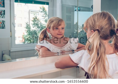 close up portrait of tidy beautiful girl with braid hairdo looking into bathroom mirror