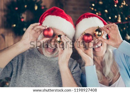 Close-up portrait of two cheerful positive playful nice grey-haired people married spouses grandma grandpa holding round glossy shiny toys covering closing eyes fooling good mood indoors opened mouth
