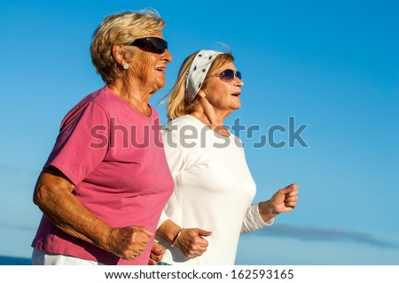 Close up portrait of two elderly women jogging outdoors.