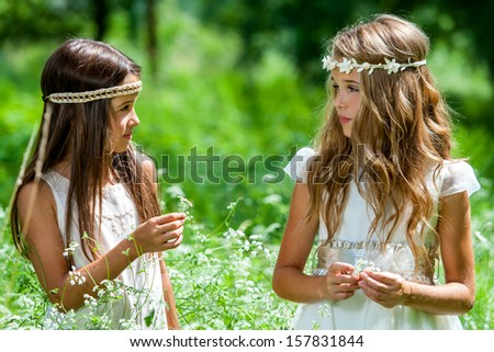 Close up portrait of two girls standing in flower field.