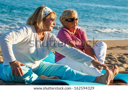Close up portrait of two golden age women doing stretching exercises together on beach.