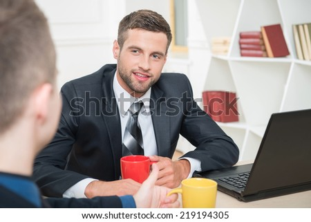 Close-up portrait of two handsome businessmen in suits having a coffee-break in office sitting at the table, with selective focus on one smiling businessman and another sitting back to the camera