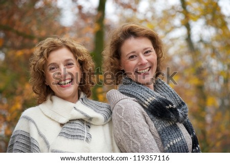 Close up portrait of two mature women smiling in the park