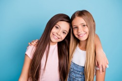 Close-up portrait of two people nice cute lovable tender gentle lovely sweet charming dreamy attractive cheerful straight-haired pre-teen girls siblings cuddling isolated on blue turquoise background
