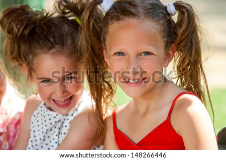 Close up portrait of two smiling pony tailed girls together outdoors.