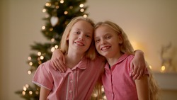 Close Up Portrait Of Two Twin Sisters Hugging And Smiling Near Christmas Tree, Holidays Christmas Time At Home Holidays And Celebrations Concept, Decorated For Christmas