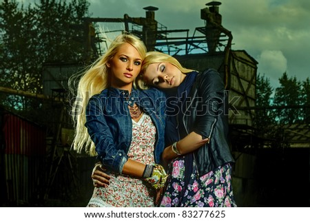Close-up portrait of two voluptuous girls in industrial background - stock photo