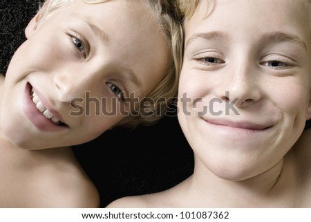 Close up portrait of two young brothers laying down with heads together.