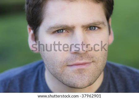 Close up Portrait of Unshaven Male Outdoors Wearing Blue T-Shirt