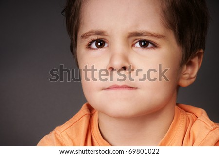 Close-up portrait of upset little boy, studio shot