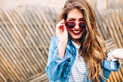 Close-up portrait of white european smiling girl with long hair and red lips. Attractive young laughing woman dropped stylish sunglasses in surprise on the blur background. White accessories