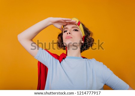 Close-up portrait of winsome girl in blue shirt standing in confident pose on yellow background. Brave female model in crown and red mantle fooling around in studio.